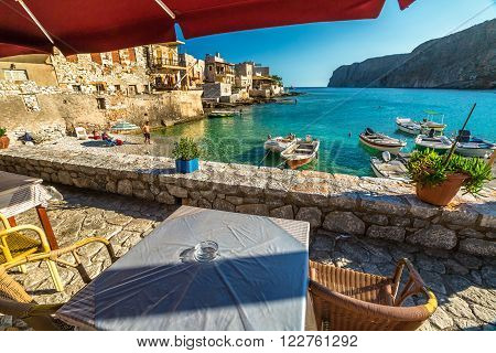 Gerolimenas village, Mania Peninsula, Lakonia, Peloponnese, Greece - August 23, 2015: Typical tavern greek on waterfront between mountains and bay with tropical waters, stone beach and fishing boats.
