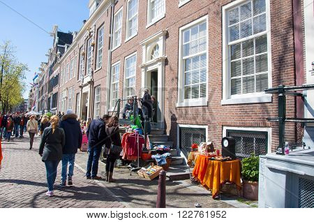 AMSTERDAMNETHERLANDS-APRIL 27: Locals display bric-a-brac outside their homes for sale on King's Day on April 27 2015. King's Day is the largest open-air festivity in Amsterdam.