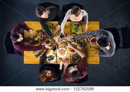 Top view creative photo of friends sitting at wooden vintage table. Friends of six having dinner. They with plates full of delicious meal and glasses with drinks. All clinking glasses