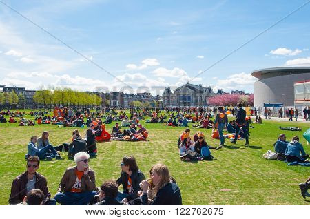 AMSTERDAM-APRIL 27: People relax at the Museumplein on King's Day on April 272015. Museumplein is a public space between three museums: Rijksmuseum Van Gogh Museum and Stedelijk Museum.