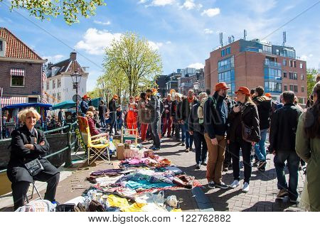 AMSTERDAM-APRIL 27: Locals display their old things for sale in old center of Amsterdam on King's Day on April 27 2015. Kings Day is the biggest festival celebrating the birth of Dutch royalty.