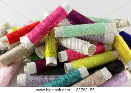 Multicolored bobbins of thread on white closeup