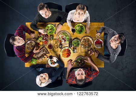 Top view creative photo of friends sitting at wooden vintage table. Friends of six having dinner. They with plates full of delicious meal and glasses with drinks. All looking at camera