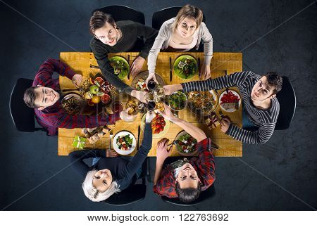 Top view creative photo of friends sitting at wooden vintage table. Friends of six having dinner. They with plates full of meal and glasses with drinks. All looking at camera and clinking glasses