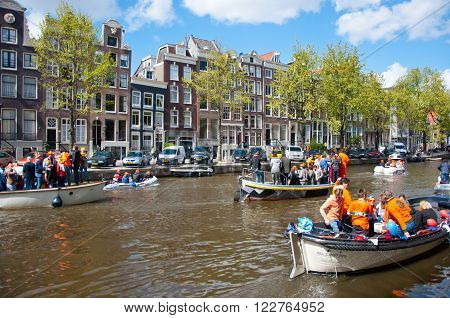 AMSTERDAMNETHERLANDS-APRIL 27: Amsterdam canal full of boats during King's Day on April 27 2015 the Netherlands. King's Day is the largest open-air festivity in Amsterdam the Netherlands.