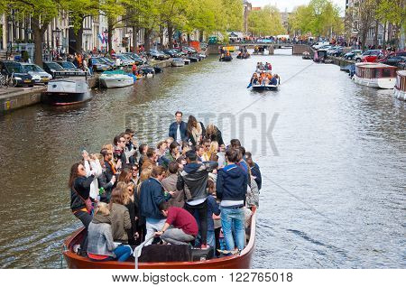 AMSTERDAM-APRIL 27: King's Day boating through canals on April 27 2015 in Amsterdam the Netherlands. King's Day (Koningsdag) is held on 27 April (the king's birthday) every year.