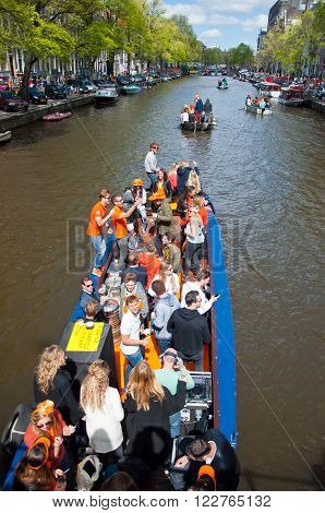 AMSTERDAM - APRIL 27: People on Party Boat with unlimited beer soda and wine aboard celebrate King's Day on April 27, 2015. King's Day is the largest open-air festivity in Amsterdam.