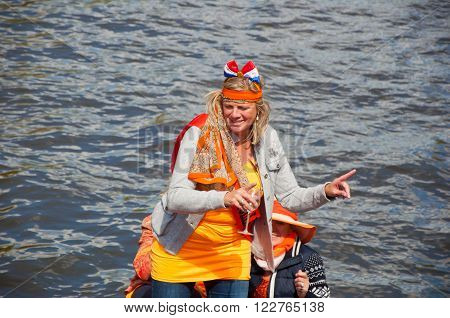 AMSTERDAM - APRIL 27: Active participant on boat party during King's Day on April 27, 2015 in Amsterdam the Netherlands. Kings Day is the biggest festival celebrating the birth of Dutch royalty.