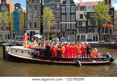 AMSTERDAM, NETHERLANDS - APRIL 27: Boat party on Amsterdam canal during King's Day on April 27, 2015 in Amsterdam. King's Day is the largest open-air festivity in Amsterdam the Netherlands.