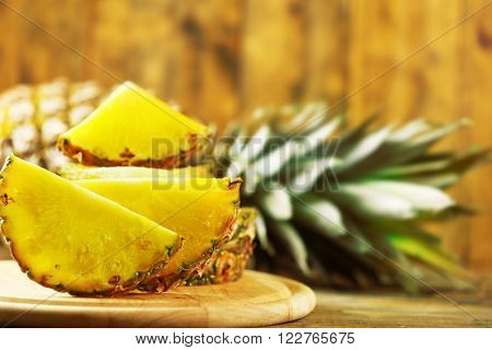 Juicy pineapple slices on wooden cutting board, close up