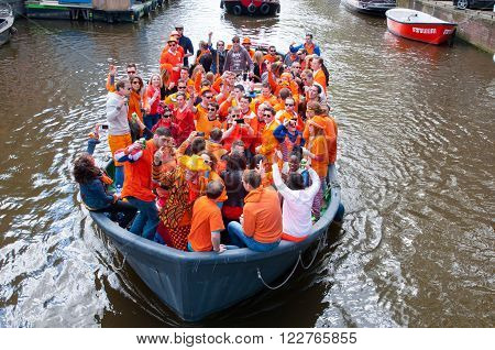 AMSTERDAMNETHERLANDS-APRIL 27: Crowd of people dressed in orange celebrate King's Day in a boat on April 272015 in Amsterdam. King's Day is the largest open-air festivity in Amsterdam.