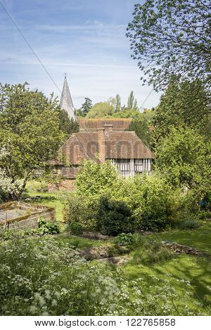 View across a garden of a half-timbered cottage with the church spire behind it