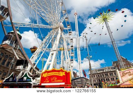 AMSTERDAM, NETHERLANDS-APRIL 27: Attractions on Dam Square during King's Day on April 272015 in Amsterdam. King's Day is the largest open-air festivity in Amsterdam.