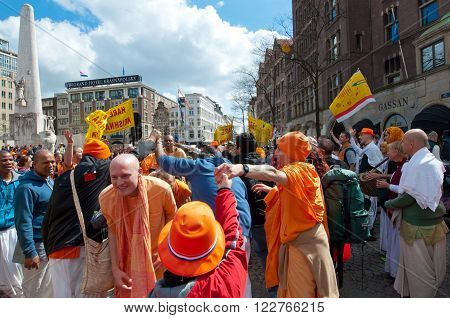AMSTERDAM, NETHERLANDS-APRIL 27: Locals and tourists in orange celebrate King's Day on Dam Square on April 272015 in Amsterdam. King's Day is the largest open-air festivity in Amsterdam.