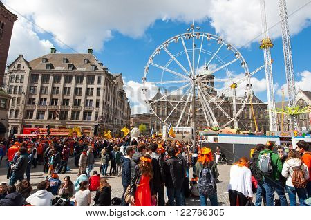 AMSTERDAMNETHERLANDS-APRIL 27: Dam Square full of people in orange during King's Day on April 272015 in Amsterdam. King's Day is the largest open-air festivity in Amsterdam.