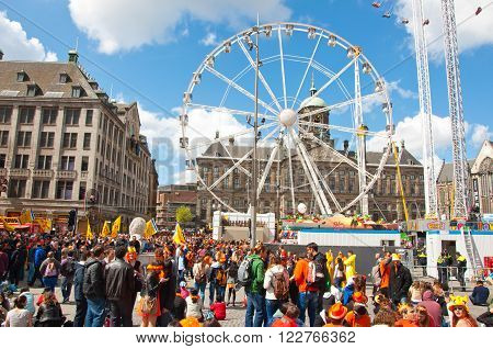 AMSTERDAM - APRIL 27: Dam Square with crowd of people during King's Day on April 27, 2015 in Amsterdam Netherlands. King's Day is a national holiday celebrated on April 27th.