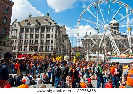 AMSTERDAM - APRIL 27: Crowd of people in orange on Dam Square during King's Day on April 27, 2015 in Amsterdam Netherlands. King's Day is a national holiday celebrated on April 27th.