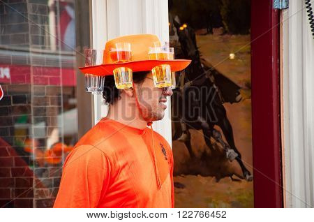 AMSTERDAMNETHERLANDS-APRIL 27: Local in orange on the street on King's Day on April 2727 in Amsterdam. The King Day is celebrated every year in April 27.