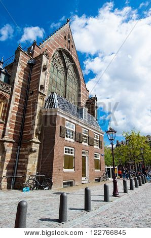 Amsterdam-April 27: Oude Kerk in Amsterdam's main red-light district on April 272015 in Amsterdam the Netherlands. The Oude Kerk is Amsterdam's oldest parish church consecrated in 1306.