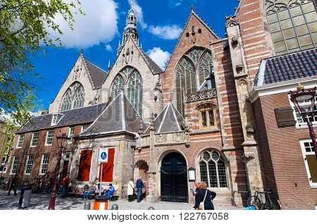 Amsterdam-April 27: Oude Kerk in De Wallen tourists go sightseeing on April 272015 in Amsterdam the Netherlands. The Oude Kerk is Amsterdam's oldest parish church consecrated in 1306.