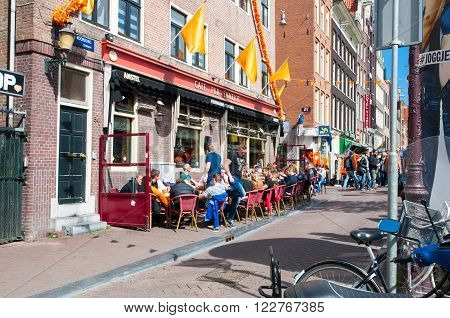 Amsterdam-April 27: Company of young men celebrate King's Day in a local outside cafe in red-light district of Amsterdam on April 272015 the Netherlands.