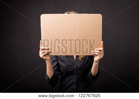 Woman hiding her face  behind empty cardboard plate