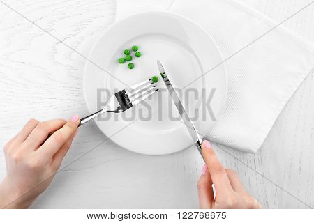 Female hands holding fork and knife on plate with green peas on wooden table, top view