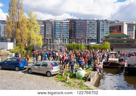 AMSTERDAM - APRIL 27: People on the river front wait for the boat to celebrate King's Day on April 27, 2015 the Netherlands. The King Day is celebrated every year in April 27.