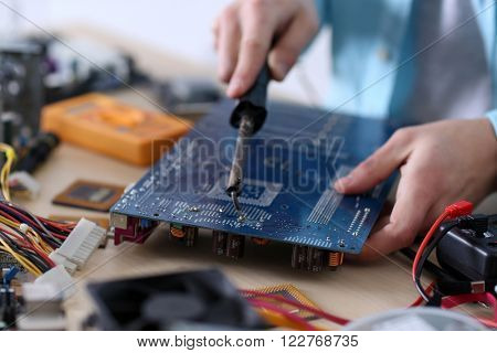 Young man working with soldering iron in service center