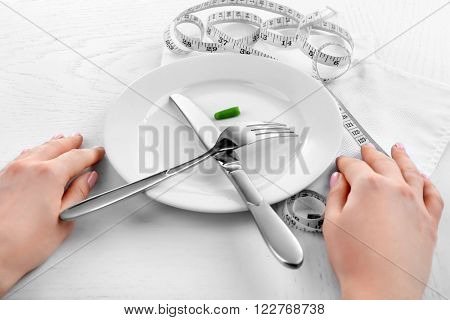 Female hands holding knife and fork with french bean on wooden table with measuring table closeup