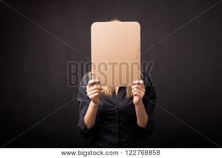 Woman holding empty cardboard in front of her face