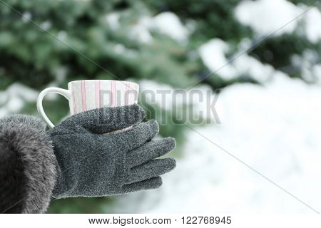 Female hands holding cup of hot drink at the winter park