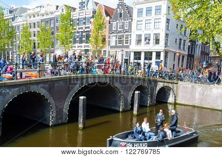 AMSTERDAMNETHERLANDS-APRIL 27: Trade fair on the bridge on King's Day on April 27 2015 in Amsterdam Netherlands.