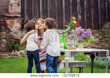 Beautiful Mom, Having Coffee In A Backyard, Young Cute Child Giving Her Present And Flowers