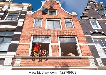 AMSTERDAMNETHERLANDS APRIL 27: Local youth celebrate King's Day in city center on April 27 2015 in Amsterdam. King's Day is the biggest street party of the year.