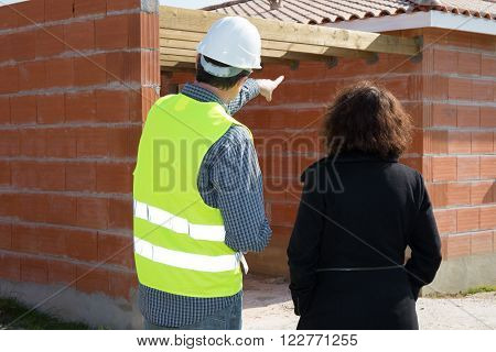 Constructions workers looking at a unfinished house with bricks wall