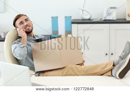 Businessman with moving box talking on the phone in office