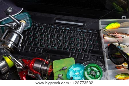 Fishing Tackles On Keyboard A Black Notebook