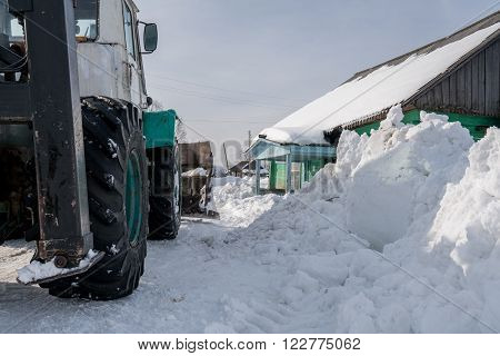 Winter time. Tractor cleans snow in village, close-up