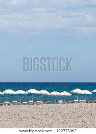 many white parasols and deck chairs on the sandy beach with white sand and blue sea and sky