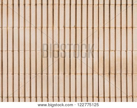 large surface of an old wall of beige colored shaped concrete blocks with coarse seams and joints with vertical stripes outdoors