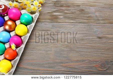 Easter eggs with flowers in tray on wooden background