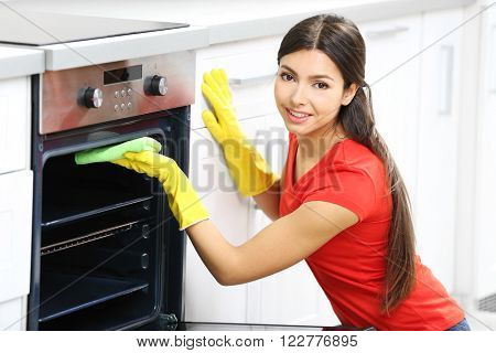 Beautiful woman in protective gloves cleaning oven with rag