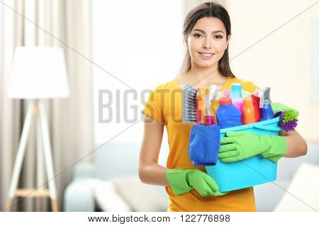 Beautiful woman with bucket of cleaning supplies