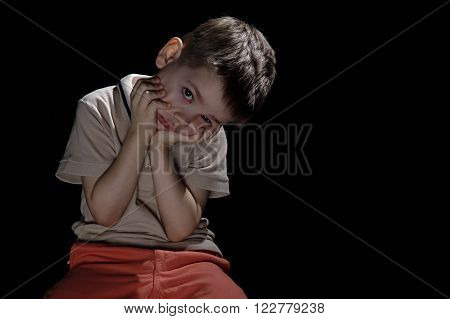 Bored grimacing little boy with hands on face on black background