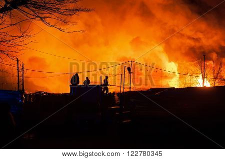 Firefighters battles storage fire. Silhouette of firefighters on the roof. Night Scene with a fiery glow in the background.