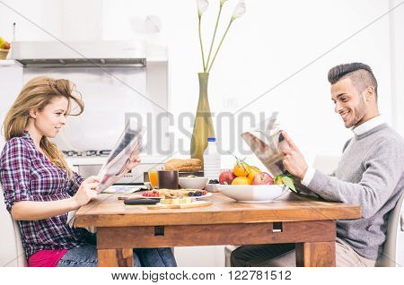 Couple reading newspapers at breakfast in the morning