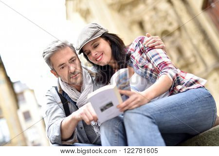 Couple of tourists looking at city guide