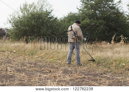DIKANKA UKRAINE - SEPTEMBER 30 2015: Country farmer working mows dry grass trimmer in garden