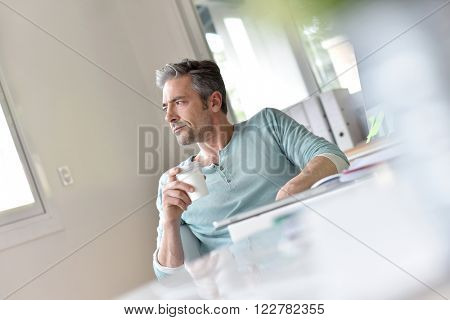 Man in office relaxing with cup of coffee